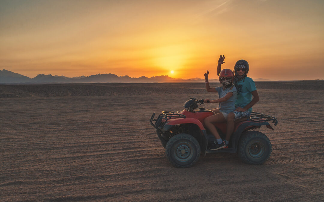 two people riding on an ATV that was transported to the beach with a toy hauler