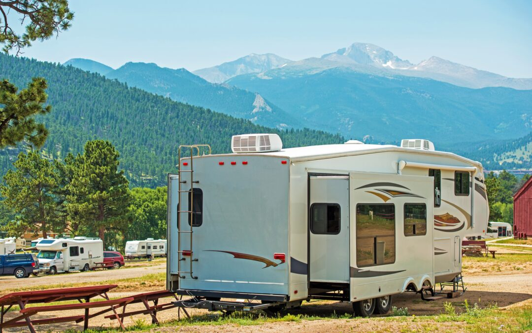 fifth wheel RV parked next to picnic table with mountain range in the distance