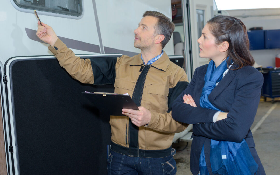 man showing woman new motorhomes for sale at dealership